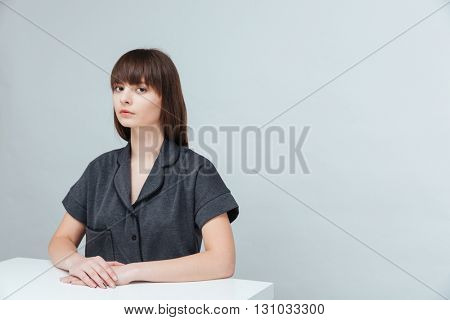 Young casual woman sitting at the desk and looking at camera isolated on a white background