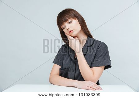Pensive woman sitting at the table isolated on a white background