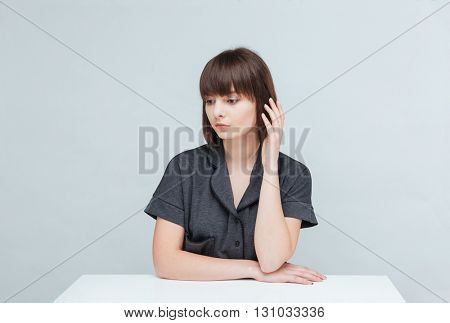 Thoughtful woman sitting at the table isolated on a white background