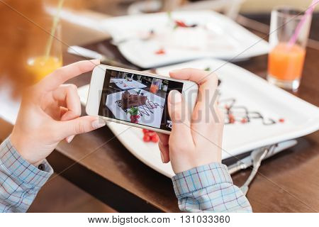 Hands of young woman using mobile phone and taking pictures of chocolate dessert on white plate in cafe