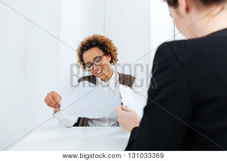 Smiling african american young businesswoman having job interview and filling application in office