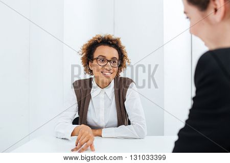 Cheerful beautiful african american young businesswoman interviewing candidate for new position in office