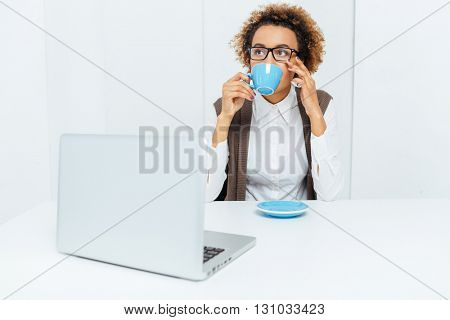 Pensive african american young businesswoman sitting at workplace and drinking coffee