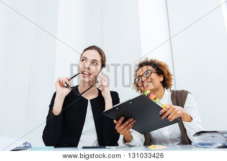 Two happy inspired young businesswomen with clipboard dreaming and smiling at workplace