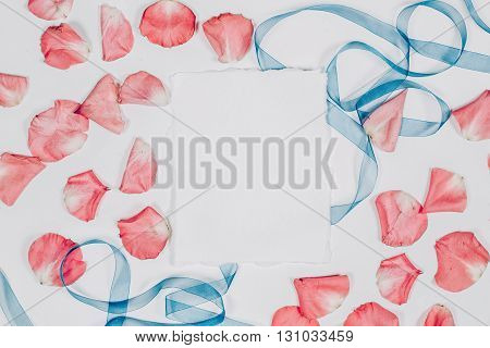 emty paper sheet with pink petals and blue ribbon. Flat lay, top view, copyspacecx