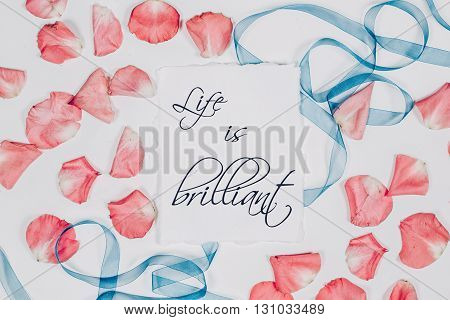 quote Oh beautiful day written in calligraphy style on paper with pink petals and blue ribbon. Flat lay, top view