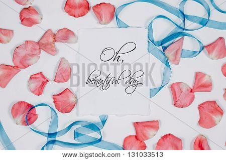 quote oh beautiful day written in calligraphy style on paper with pink petals and blue ribbon. Flat lay, top view.