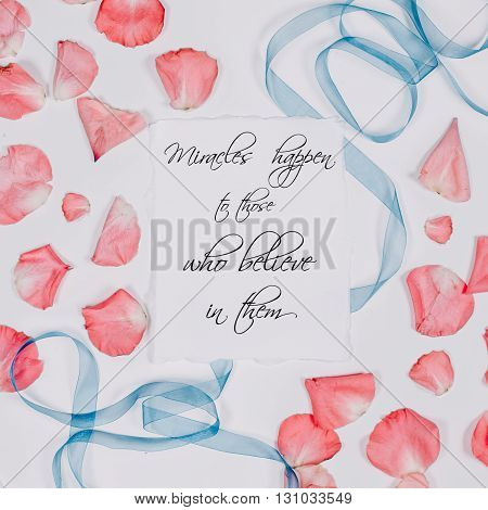 quote miracles happen written in calligraphy style on paper with pink petals and blue ribbon. Flat lay, top view
