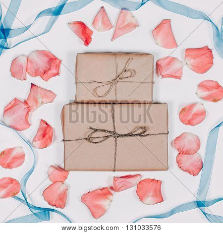 Two presents inparchment with pink petals and blue ribbon on white background. Top view, flat lay