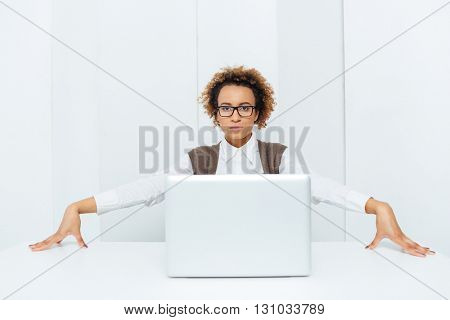 Serious african american curly businesswoman sitting and posing with laptop at the table