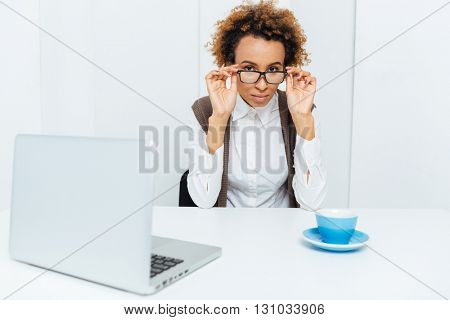 Attractive african american curly businesswoman using laptop and drinking coffee in office
