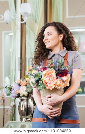 Attractive smiling young woman florist standing and holding vase with flowers in the shop