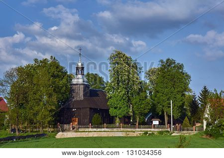 Wooden country church with belfry in Poland