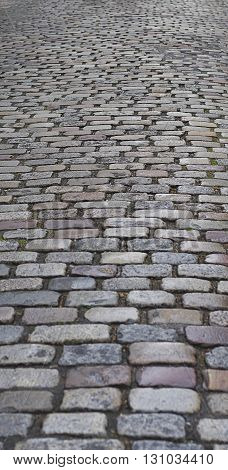 Old traditional european style long narrow cobblestone road background with granite blocks stones and brickwork pattern
