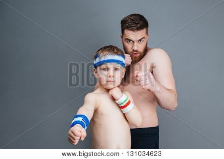 Serious bearded father and his little son punching at camera over grey background