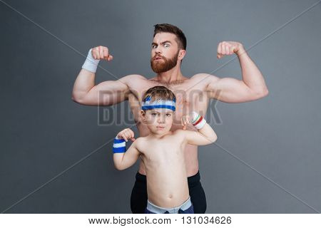 Strong bearded man and his son standing and showing biceps over grey background
