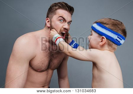 Smiling little son playing with dad beard over grey background
