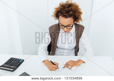 Curly african american young woman accountant sitting and writing in office