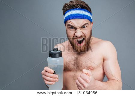 Angry shirtless young sportsman holding bottle of water and shouting over grey background