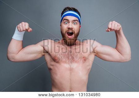 Happy amazed young sportsman standing and showing biceps over grey background