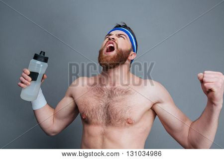 Furious bearded young sportsman with bottle of water standing and shouting over grey background