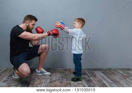 Father and little son working out in boxing gloves together over grey background