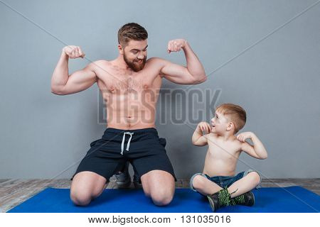 Smiling shirtless dad and son sitting on mat and showing biceps over grey background