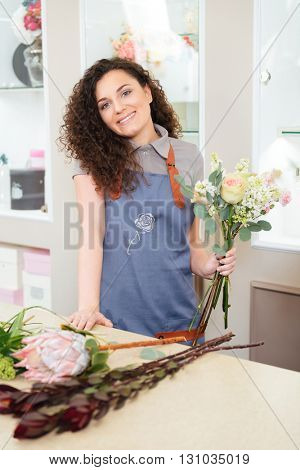 Cheerful lovely young woman florist choosing flowers and making bouquet in shop