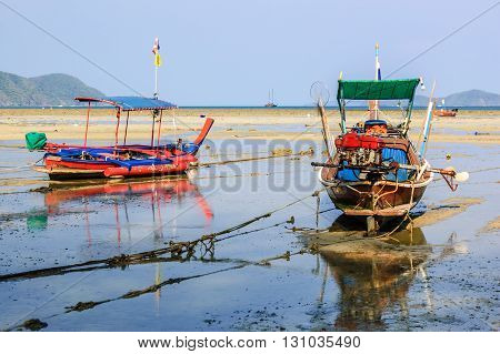 Long-tail boats stranded on Rawai beach at low tide Phuket Thailand