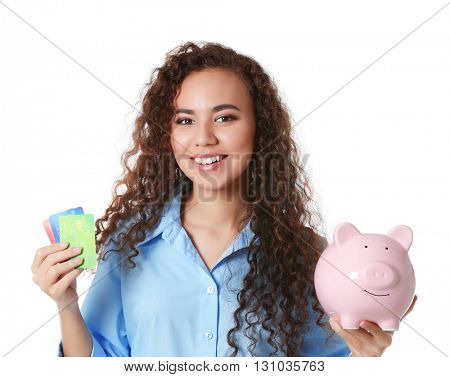 Beautiful young girl holding piggy bank and credit cards, isolated on white