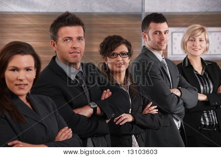 Portrait of business team standing in a row with arms crossed, smiling.