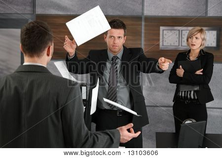 Disappointed director rejecting business report, throwing away papers, pointing out of frame.