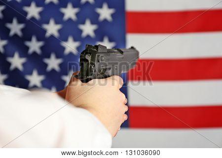 Woman holding handgun on USA national flag background