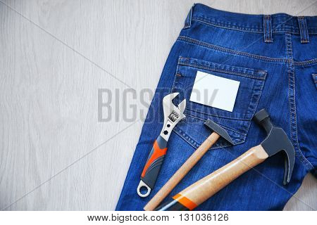 Construction tools and jeans on wooden background. Labor Day concept