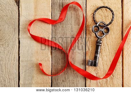 Old key and red ribbon on wooden background