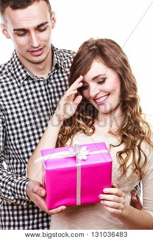 Couple holidays and happiness concept. Smiling handsome man giving his woman pink gift box isolated on white