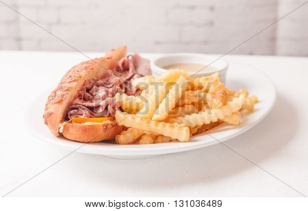 deli style sliced rare roast beef on a cheese bun with french fries and gravy
