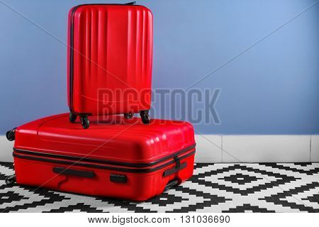 Suitcases on blue wall background
