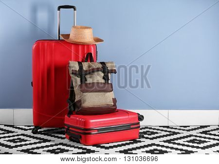 Suitcases with hat on blue wall background