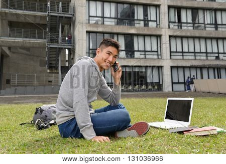 Portrait of asian student sitting use mobile phone on a grass at a campus