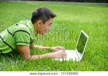 Asian student lying down use laptop at campus grass