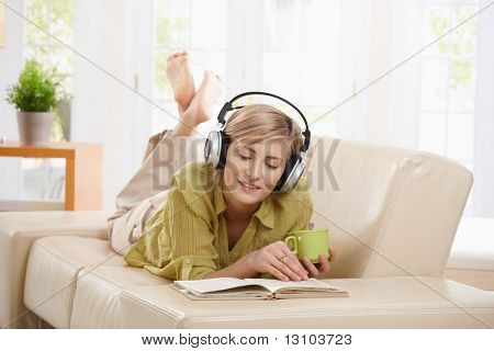 Woman drinking coffee, lying on couch reading book, wearing headphones at home.