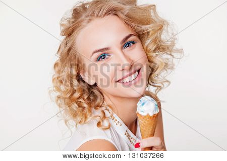 Beautiful girl with curly hair and perfect smile eating blue ice-cream in waffle cone