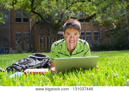 Asian male college student lying down use laptop at campus glass