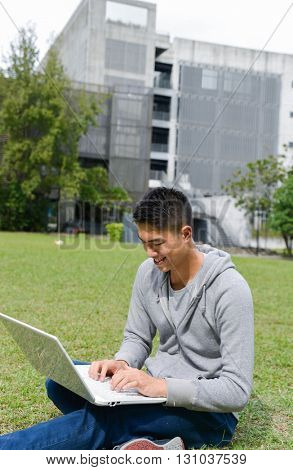 Portrait of asian student sitting use laptop on a grass at a campus