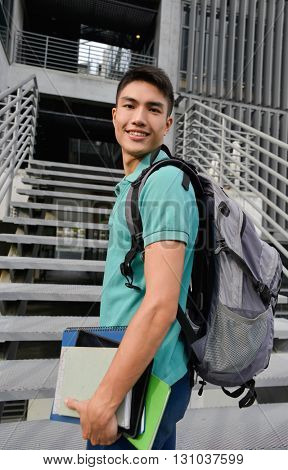 portrait of male college student holding book at campus