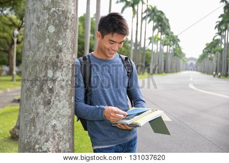portrait of male college student holding book with bag at campus