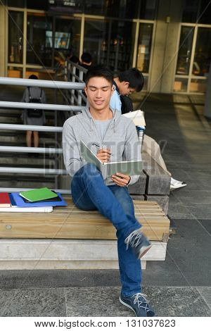 handsome male college student sitting use laptop at campus