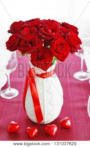 Vase with red roses on a holiday served table