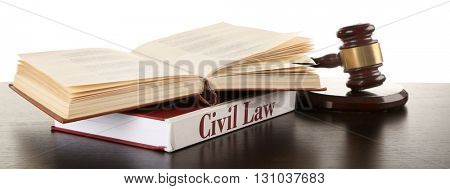 Gavel and books on wooden table on white background
